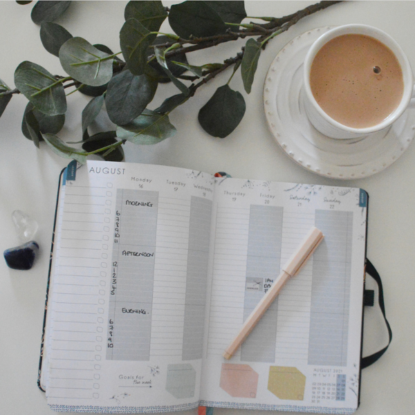 Open diary with a cup of coffee, highlighting how useful the planner is to see the week ahead